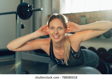 Smiling active fit young woman working out doing pilates exercises in a gym balancing over a ball