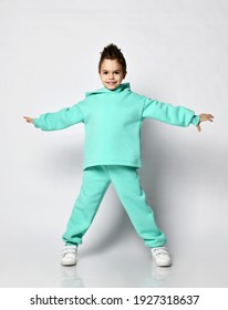 Smiling active kid boy with stylish haircut in modern green, mint color sportswear hoodie, pants and white sneakers stands holding hands up spread over white background