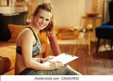 smiling active sports woman in sport clothes with clipboard and pen building athletics plan in the modern house.