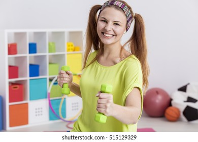 Smiling active teenager wearing headband holding two dumbbells