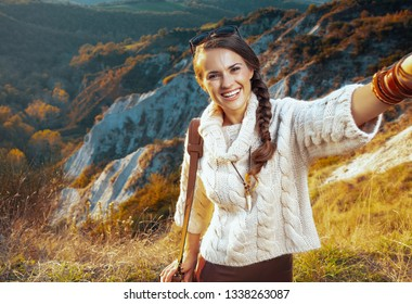 smiling active woman hiker in hiking clothes with bag on summer Tuscany trekking taking selfie.