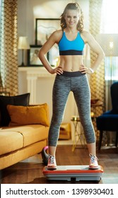 smiling active woman in sport clothes at modern home training using vibration power plate.