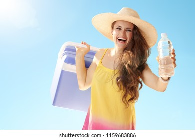 smiling active woman in straw hat with blue plastic cooler box giving bottle of cold water against blue sky