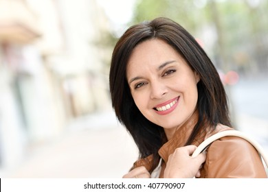 Smiling active woman walking in street