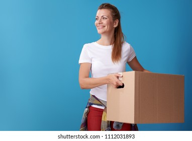 smiling active woman in white shirt with a cardboard box looking at copy space against blue background