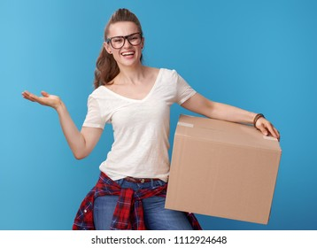 smiling active woman in white shirt with a cardboard box presenting something on empty palm isolated on blue