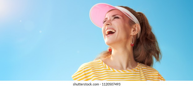 smiling active woman in yellow shirt against blue sky looking into the distance