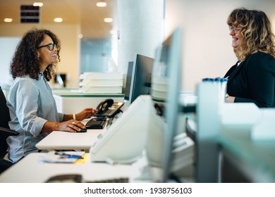 Smiling administrator talking with a woman standing at reception desk. Woman visiting municipal office for work and talking with the receptionist.