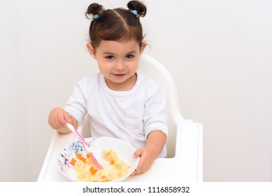 Smiling adorable girl with funny pigtails eat soup with spoon. Child little baby eats food sitting in kids high eat chair / Baby Dining Chair.