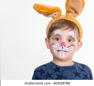smiling adorable kid with paintings on his face and ears on