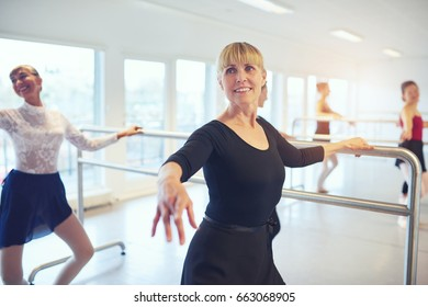 Smiling adult ballerinas standing and doing exercises in ballet class.