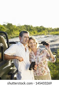 Smiling adult couple standing by jeep with binoculars