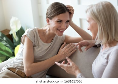 Smiling adult daughter listening to older mother, talking, sitting on cozy couch at home, happy young woman and mature mum or grandmother chatting, having fun, sharing news, two generations