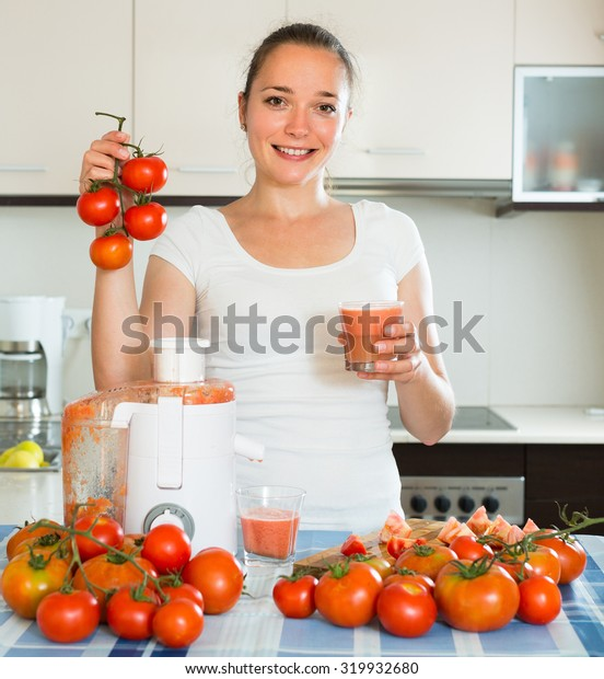 Smiling adult girl making juice from tomatoes at home kitchen
