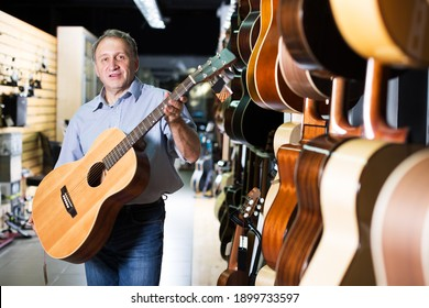 Smiling adult guitarist is holding modern acoustic guitar in music store