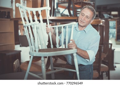Smiling adult man is buying antique armchair in store.