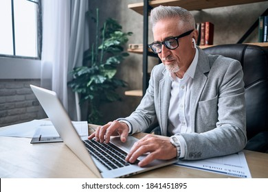 Smiling adult man in glasses working in the office while typing on laptop while using wireless headphones. Business career concept