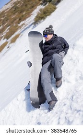 e03cc3e9389 Smiling adult man in mirrored sunglasses relaxing in snow with snowboard