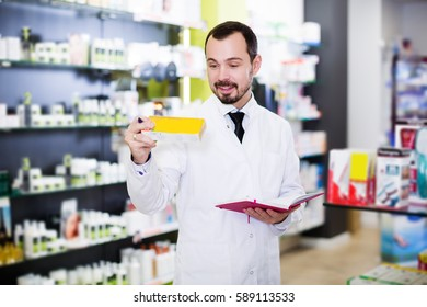Smiling adult man pharmacist writing down assortment of drugs in pharmacy