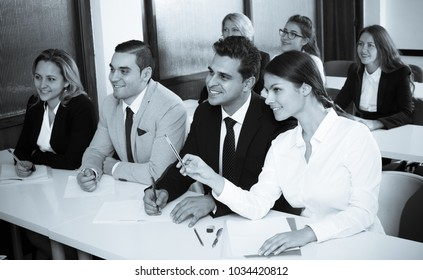 Smiling adult students sitting at the desks at business training . Selective focus