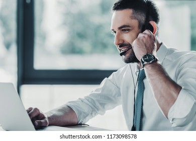 smiling adult support hotline worker with laptop at workplace