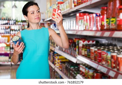 Smiling adult woman choosing tomato paste at the modern supermarket