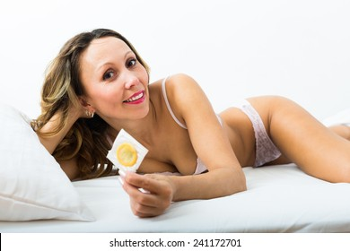 Smiling adult woman holding condom in bed