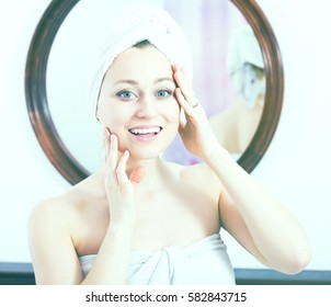 Smiling adult woman with a towel on the head having a look at her face at the mirror on the wall