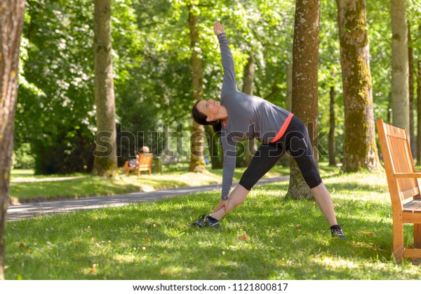 Smiling adult woman wearing sportswear stretching in park on sunny day