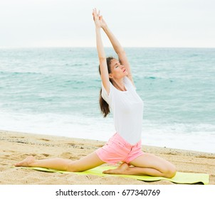 Smiling adult woman in white T-shirt is practicing stretching on the beach.