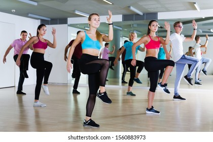 Smiling adults of different ages dancing at dance class