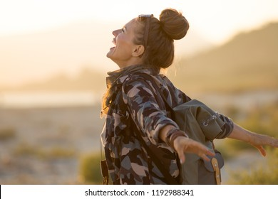 smiling adventure woman in hiking gear rejoicing against mountain and ocean landscape at sunset