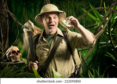 Smiling adventurer finding a huge diamond in the jungle with explorer equipment.