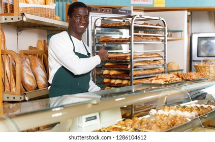 Smiling African American baker wearing apron giving thumbs up while working behind counter in small bakery