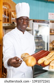 Smiling African American bakery chef offering appetizing freshly baked bread and pastry in small bakery