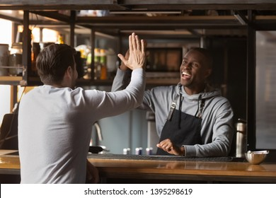Smiling African American barista giving high five with client, excited bartender wearing apron standing behind bar counter, greeting friend or regular customer in coffeehouse, celebrating success