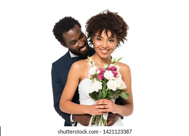 smiling african american bridegroom hugging attractive bride holding flowers isolated on white
