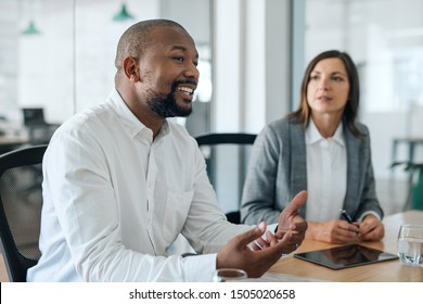 Smiling African American businessman discussing work with a group of colleagues during a meeting together in an office boardroom