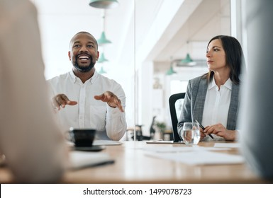 Smiling African American businessman explaining his ideas to a group of coworkers during a meeting together in an office boardroom