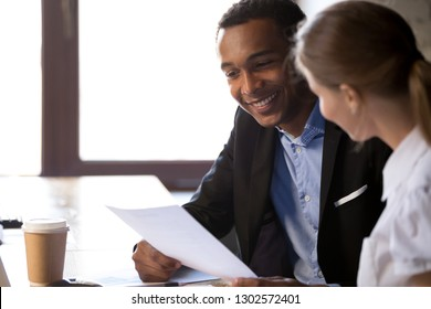 Smiling African American businessman holding female applicant cv, talking with candidate at work interview in office, excited black employer read employee resume at hiring. Recruitment concept