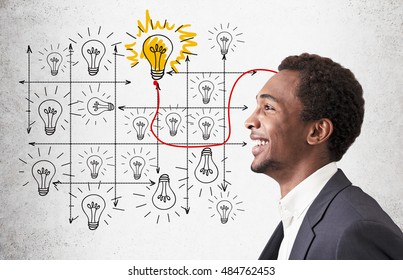 Smiling African American businessman standing near concrete wall with light bulb grid and one bulb shining. Concept of solution finding.