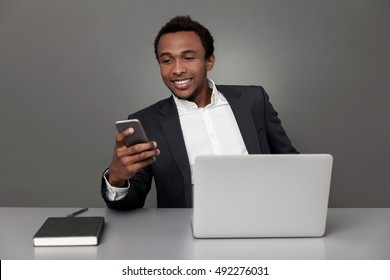 Smiling African American businessman is texting to his friend. Concept of working and not resting enough is bad for you