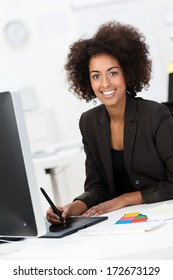 Smiling African American businesswoman at her desk using a tablet an stylus to draw or enter data on her desktop computer