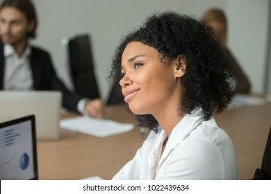 Smiling african american businesswoman looking to future thinking of business success at meeting, dreamy absent-minded black employee dreaming of vacation or making career plans, head shot portrait