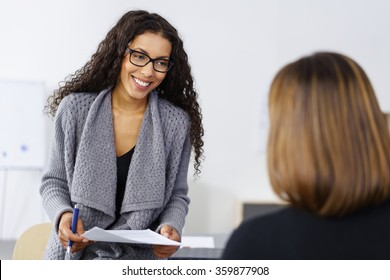 Smiling African American businesswoman in a meeting with a colleague as they discuss a document together