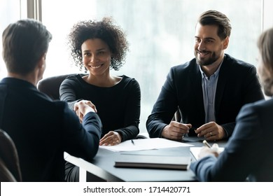 Smiling African American businesswoman shaking business partner hand at meeting, greeting each other, celebrating making good successful deal, signing contract, sitting at table in boardroom