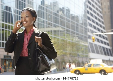 Smiling African American businesswoman using mobile phone on street against building