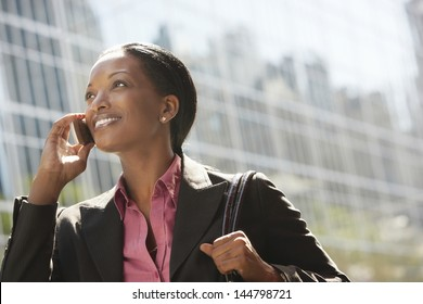 Smiling African American businesswoman using mobile phone against building