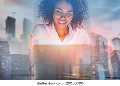 Smiling African American businesswoman working with laptop in her office with double exposure of cityscape. Toned image