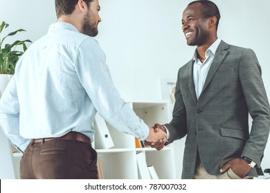 smiling african american and caucasian businessmen shaking hands